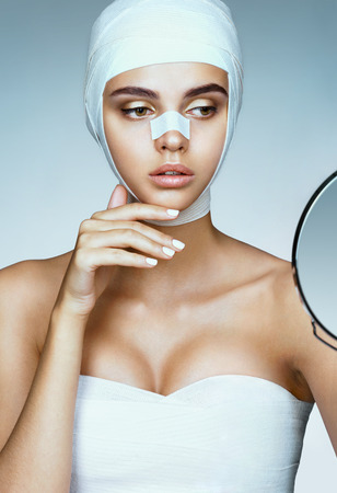 Mooie vrouw na plastische chirurgie, kijkend in de spiegel. Foto van vrouw gewikkeld in medische verbanden. Schoonheid concept