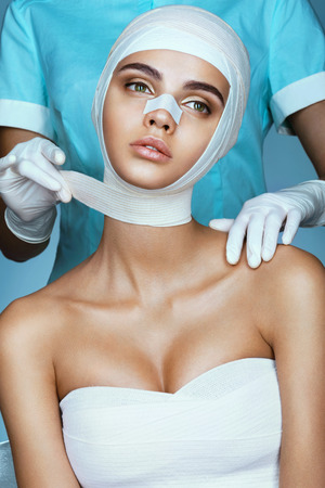 整形外科医は若い美しい女性の頭に包帯を巻きます。整形外科術後後の美しい女性の写真。
