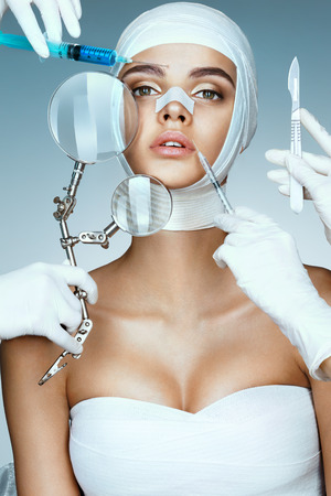 Beauty victim wrapped in medical bandages while doctors with syringes, scalpels and magnifying glass near her face. Beauty concept