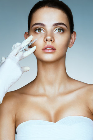 Beautiful young woman gets beauty injection in eye area from beautician. Portrait of young woman getting cosmetic injection. Clean Beauty concept Stock Photo