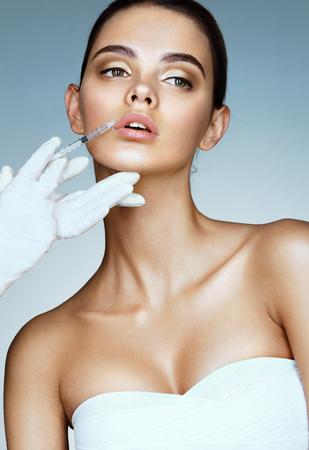 아름 다운 여자 얼굴과 미용사 손으로 주사기. 닥터는 입술에 미용 주사를합니다. 클린 뷰티 컨셉