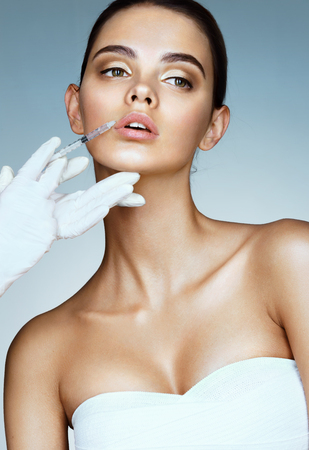 Beautiful woman face and beautician hands with syringe. Doctor makes cosmetic injection in the upper lip. Clean Beauty concept Archivio Fotografico