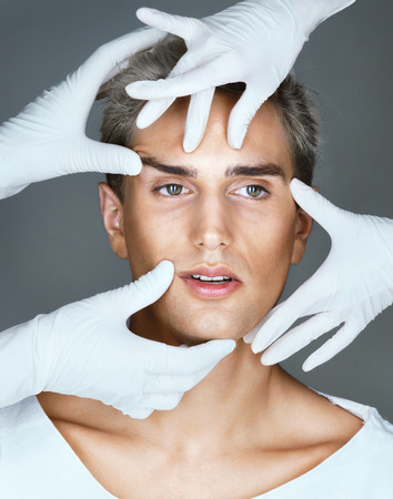 Facelift. Hands of doctors in gloves touching face of beautiful young man. Cosmetology concept