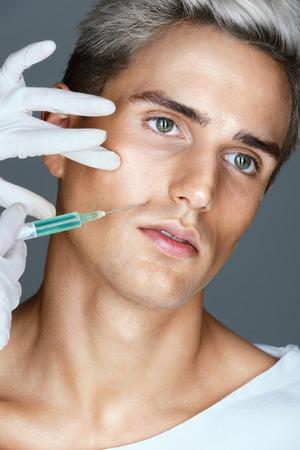 Arts die botox injectie op het gezicht van de jonge man. Foto van Man krijgt injectie in de nasolabiale plooien. Cosmetology begrip
