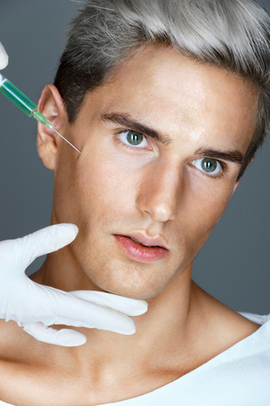 Attractive man getting lifting botox injection in cheekbones. Injections of skin rejuvenation. Cosmetic procedures