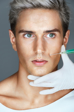 rejuvenate: Beautiful Man getting Botox injection in the nasolabial folds. Professional cosmetician making rejuvenate injection. Beauty concept