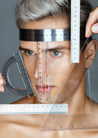 proportions of man: Perfect face proportions. Portrait of an attractive man with measuring rulers. Plastic surgery concept
