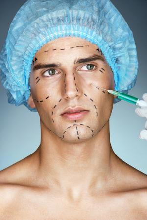 아름 다운 젊은 남자 미용사에서 눈 영역에서 보톡스 주입을 가져옵니다. 그의 얼굴에 성형 수술 지침 마크와 함께 젊은 남자의 사진. 미용 개념