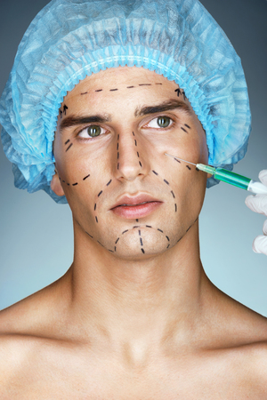 Beautiful young man gets botox injection in eye area from beautician. Photo of young man with plastic surgery guideline marks on his face. Cosmetology concept