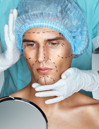 nurse hat: Beautiful Man with perforation lines on his face before plastic surgery operation. Beautician touching man face. Cosmetology. Beauty Face