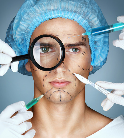 surgeons hat: Mans face and beautician hands with syringes and scalpels near his face. Surgical mark lines on eyes, nose, cheek, and jaw. Plastic Surgery concept Stock Photo