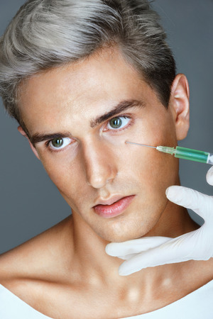 Beautiful young man gets beauty injection in eye area from nurse. Portrait of an attractive man receiving botox treatment. Cosmetology. Beauty concept Stock Photo