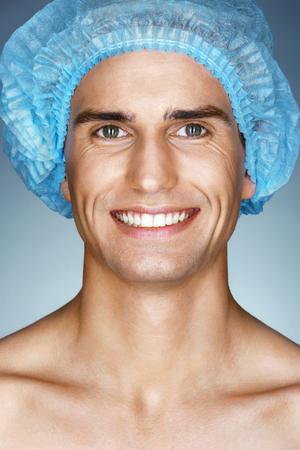 의료 모자 작동에 대한 준비가 행복 한 남자 환자. 성형 수술하기 전에 남자의 초상화입니다. 뷰티 페이스