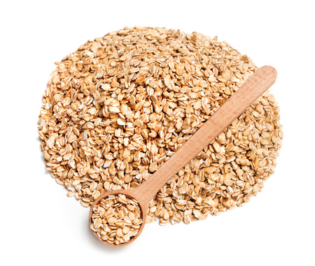 heap up: Heap of oats and spoon on white background. Diet, healthy food. Close up, top view, high resolution product Stock Photo