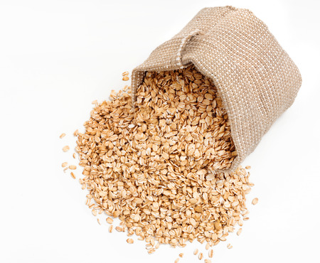 scattered on white background: Scattered oat flakes in sack on white background. Close up, top view, high resolution product