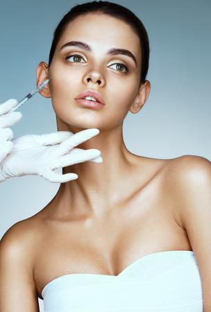 きれいな女性美容師から頬にボトックス注射を受けます。美容顔注射を取得する若い女性の肖像画。クリーン ビューティー コンセプト