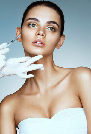 Beautiful woman receiving botox injection in cheek from beautician. Portrait of young woman getting beauty facial injections. Clean Beauty concept