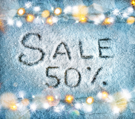 Sale 50 percent off on snow background. Merry Christmas and Happy New Year discount!! Top view. Stock Photo