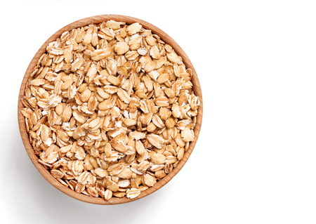 Healthy oat flakes in wooden bowl isolated on white background. Close up, top view, copy space, high resolution product