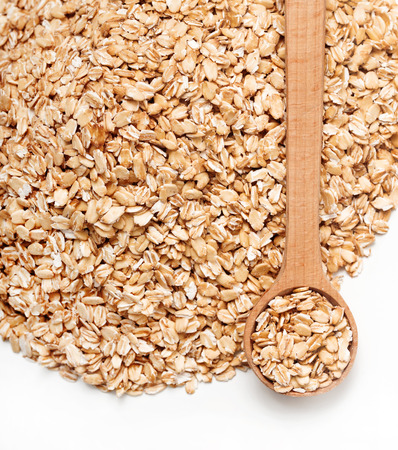 heap up: Close up heap of oats and spoon on white background. Diet, healthy food. Top view, high resolution product