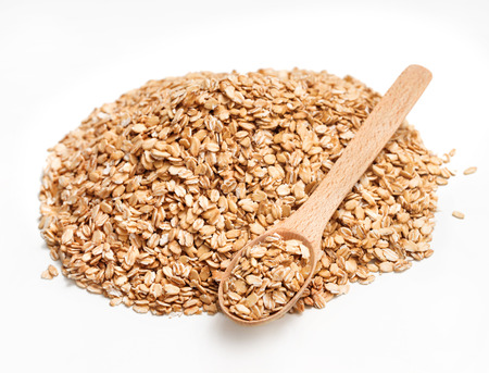 heap up: Wooden spoon and heap of oats on white background. Healthy food. Copy space. Close up, high resolution product