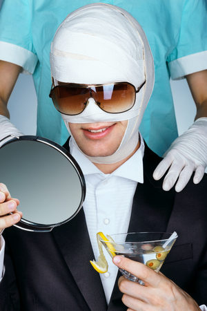 facelift: Fashionable man wrapped in medical bandages after facelift, together with nurse. Man beauty victim in sunglasses with glass of martini cocktail. Aesthetic Cosmetology concept