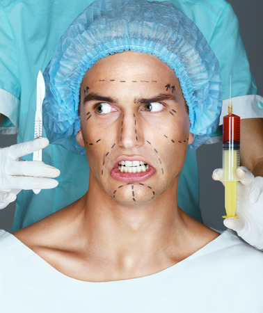 surgeons hat: Man patient with horror looks at scalpel. Nurse with syringe and scalpel near the face of scared patient. Close up of male with pencil surgical lines (forehead, eyes, nose, cheekbone and jaw)