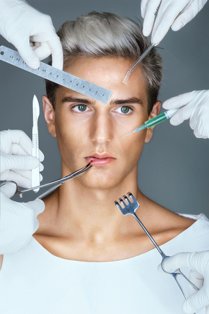 Many hands holding medical tools near face patient. Portrait of young man with surgical instruments. Concept of plastic surgery