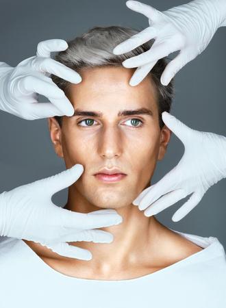 モデル チェンジ。美しい若い男の顔に触れる医療用手袋で医師の手。美容コンセプト