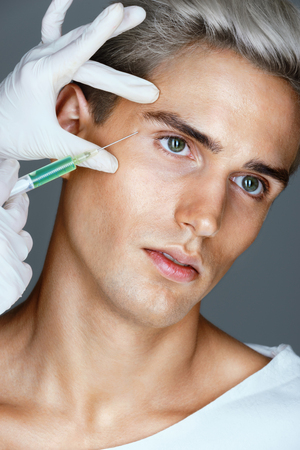 Attractive man receiving  injection in the area around the eyes. Doctor makes cosmetic injection. Beauty treatment. Stock Photo