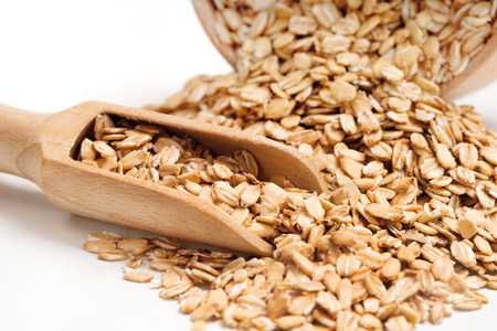 heap up: Heap oat flakes and scoop on white background. Healthy food. Close up, high resolution product.