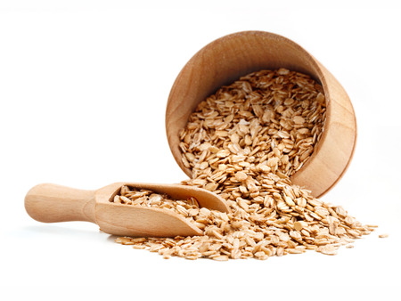 Oats scattered from wooden bowl on white background. Healthy food. Copy space, high resolution product Stock Photo