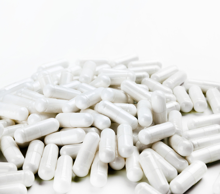 Pile of white capsules on white background. Close up, high resolution product. Health care concept