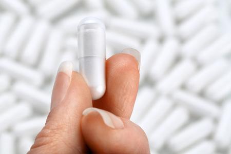 Hand met capsule op onscherpe achtergrond. Close-up, hoge resolutie product. Zorgconcept.