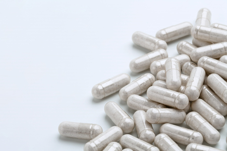 Hoop van witte capsulemedicijnen op witte achtergrond. Ruimte kopiëren. Product met hoge resolutie. Gezondheidszorg concept