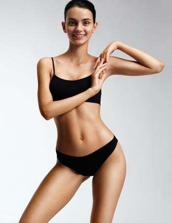 黒のランジェリーで美しい筋肉ボディを持つ少女。完璧なボディと笑顔の少女の写真。フィットネスや整形外科のコンセプト