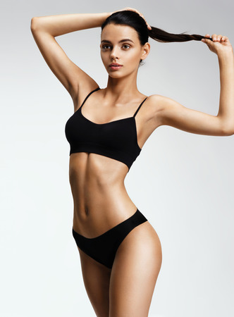 Beautiful sporty woman in black bikini posing on grey background. Photo of girl with slim toned body. Beauty and body care concept Stockfoto