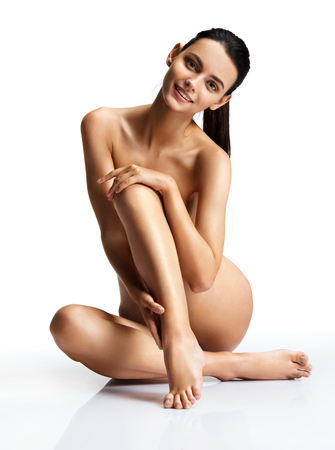 naked woman sitting: Young slim woman over white background. Photo naked female sitting on the floor touch leg. Beauty & Skin care concept
