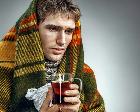 hanky: Ill Man covered with plaid blanket with hot tea. Sick man suffering cold and winter flu virus. Health care concept