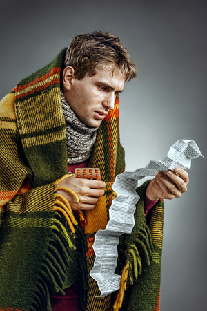 Ill Man covered with plaid blanket take medicine tablets according to instructions.  Sick man suffering cold and winter flu virus. Health care concept Stock Photo