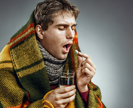 hanky: Ill Man covered with plaid blanket take medicine pill with a glass of water . Sick man suffering cold and winter flu virus. Health care concept