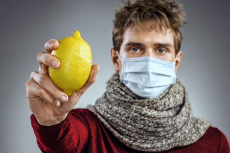 Sick man holding lemon. Photo of man wears protective mask against infectious diseases and flu. Healthcare concept Stock Photo