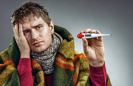 Sick man shows the temperature on the thermometer. Young man suffering cold and winter flu virus. Health care concept Stock Photo