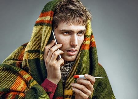 Sick man wrapped in blanket with a high temperature calling on the phone. Man suffering cold and winter flu virus. Health care concept