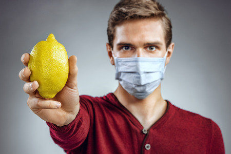 protective mask: Healthy man holding a lemon. Photo of man wears protective mask against infectious diseases and flu. Healthcare concept