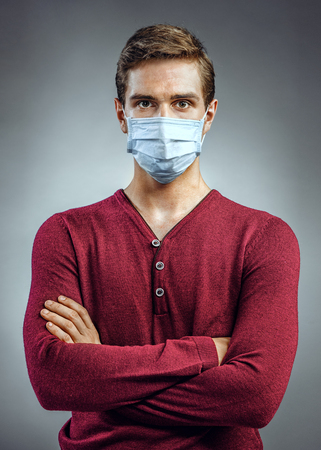 protective mask: Young handsome man with his hands folded. Photo of man wears protective mask against infectious diseases and flu. Healthcare concept