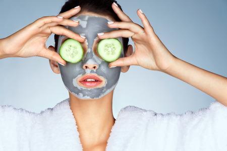 Mujer joven con una máscara de arcilla. Foto de mujer joven atractiva que cubre sus ojos con los pepinos en un fondo azul. acicalándose Foto de archivo - 71090271
