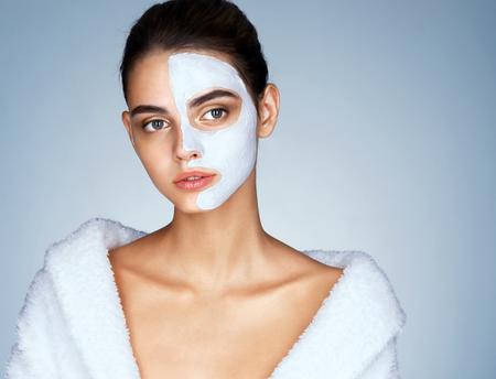 그녀의 얼굴에 화장품 마스크 화려한 여자. 흰색 목욕 가운을 입고 매력적인 갈색 머리 여자의 사진. 웰빙과 스파 개념 스톡 콘텐츠