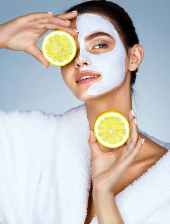 Funny beautiful model holding lemon slices up to her eyes. Photo of girl with moisturizing facial mask. Beauty & Skin care concept Archivio Fotografico