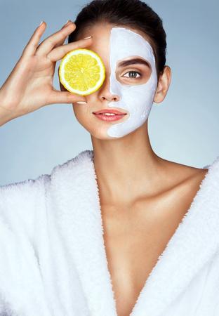 사랑스러운 소녀 그녀의 얼굴의 앞에 레몬 슬라이스를 잡고 웃 고. 소녀 수신 스파 트리트먼트의 사진입니다. 뷰티 & 스킨 케어 개념